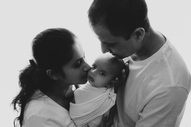 Black-and-white-image-of-a-newborn-with-his-parents-by-Lifetime-Stories-Photography