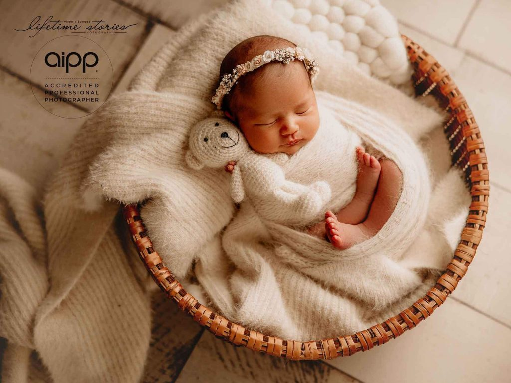 newborn baby girl posed on his back by Victoria Burcusel at Lifetime Stories Photography