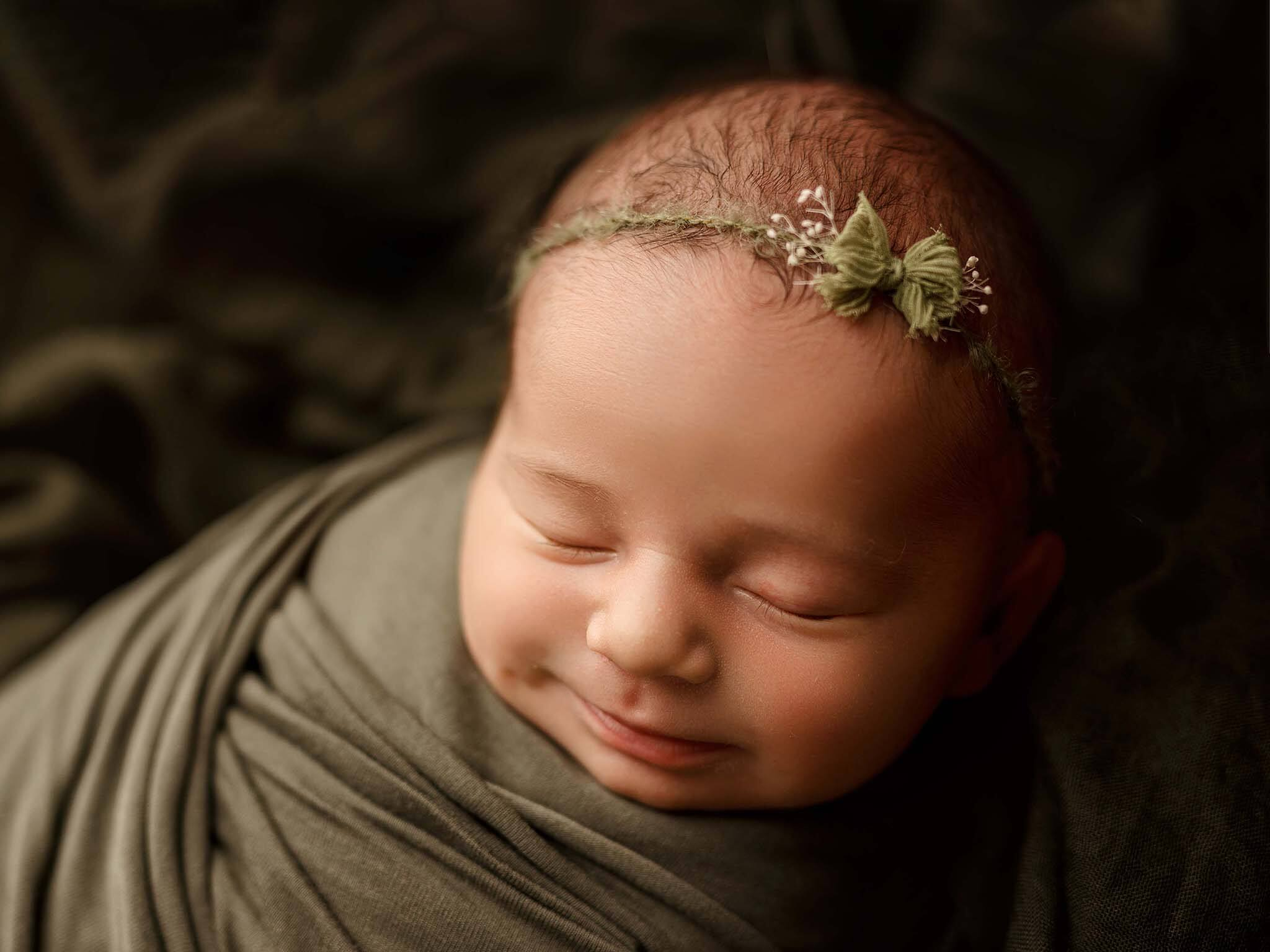 newborn phNewborn baby smiling dressed on green photographed by Lifetime Stories Photography Victoria Burcusel at her studio in Brisbane