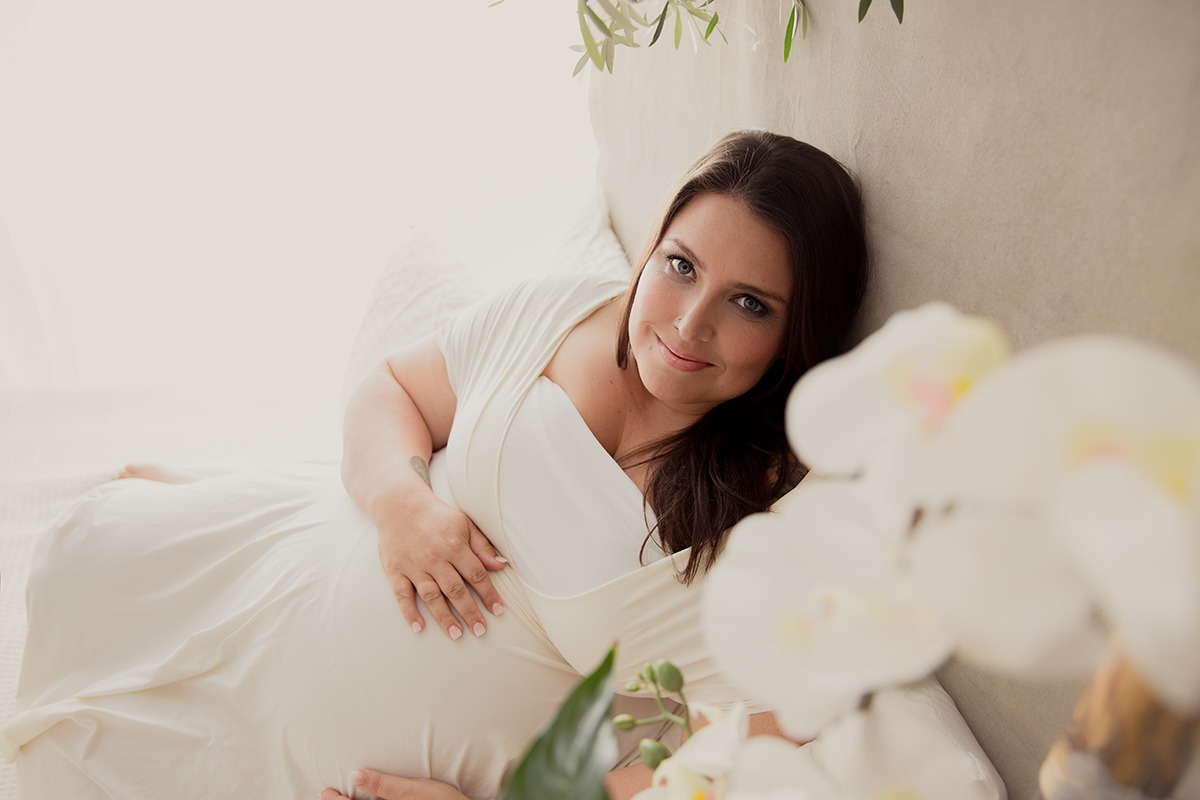 Pregnant mum laying on the bed and photographed by the Brisbane best maternity photographer Lifetime Stories Photography