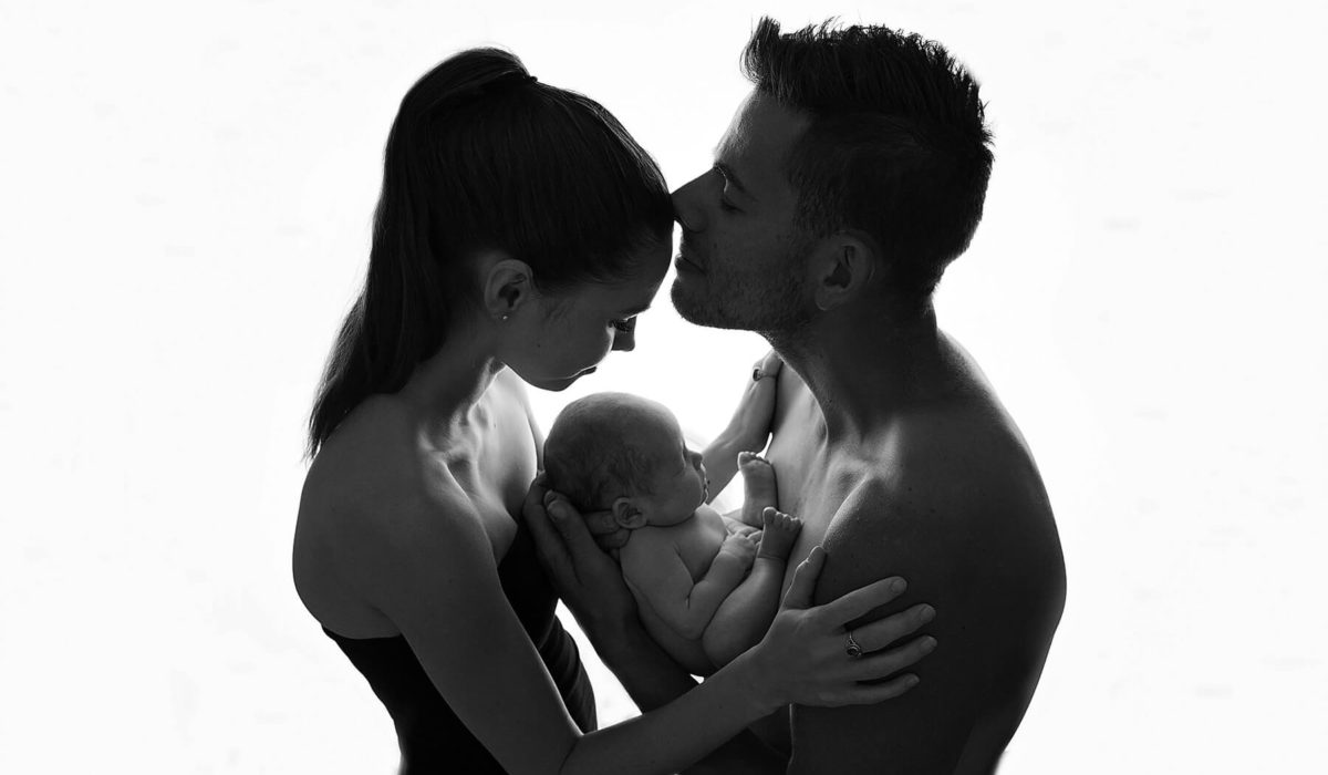 portrait of mum and dad holding the baby girl in their arms in front of a window