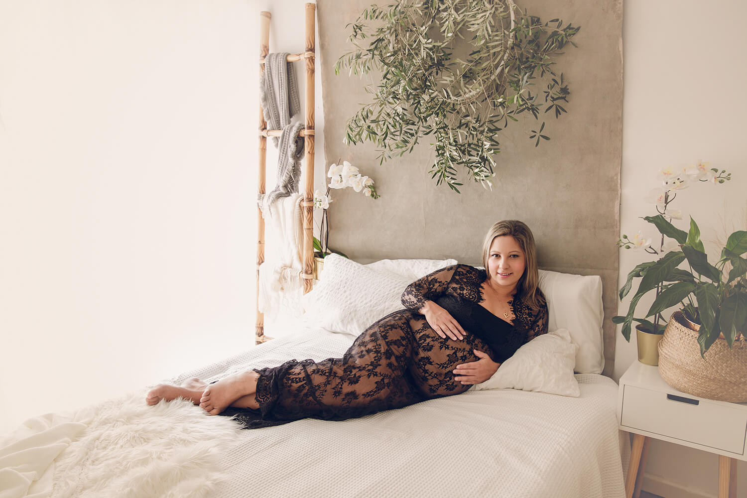 a gold coast pregnant mum dressed in a black lace dress photographed on a bed by Lifetime Stories Photography maternity photographer located in Rochedale South